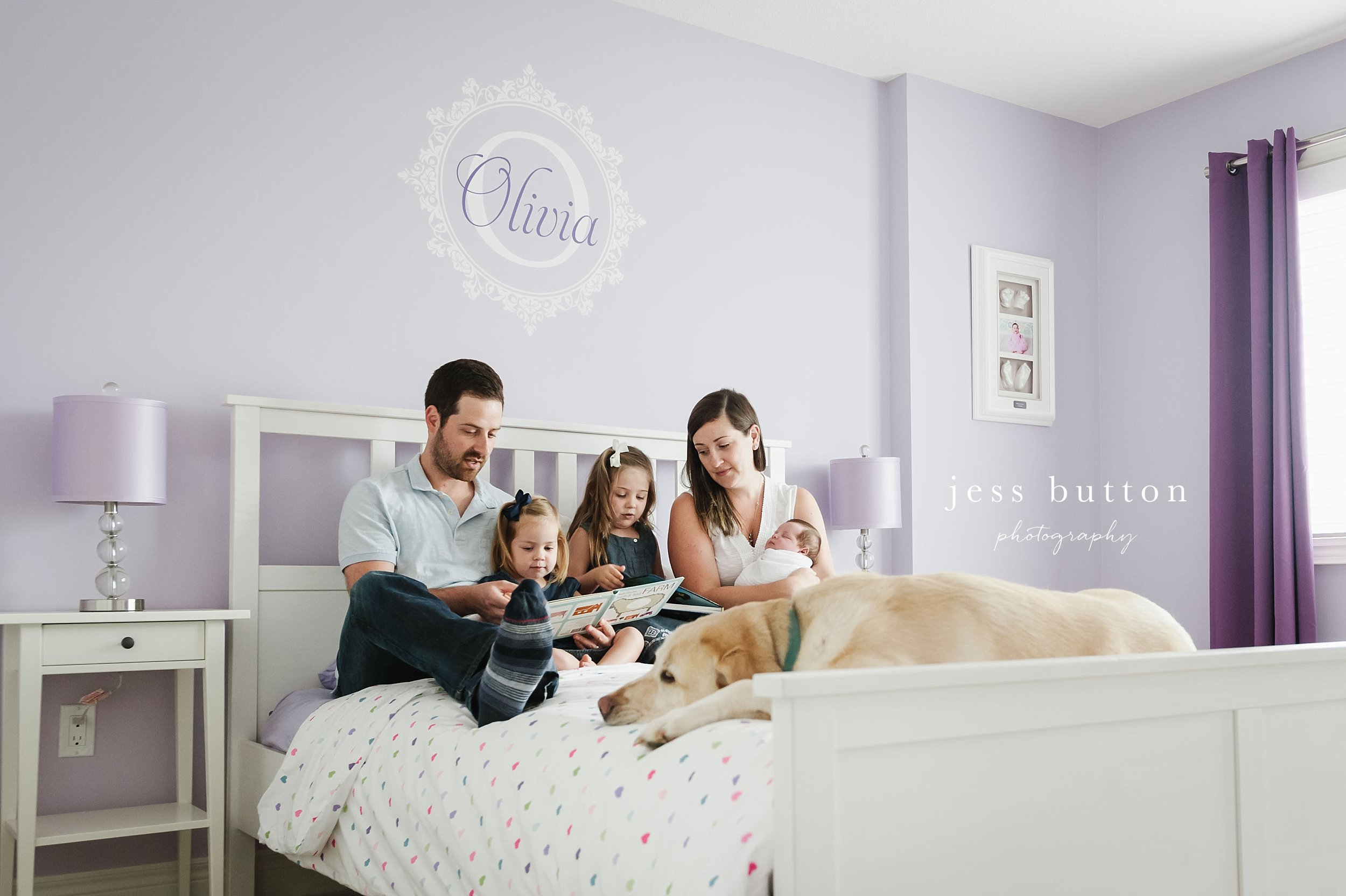 family with new baby and siblings reading in bed - Fonthill - Niagara Newborn Photography
