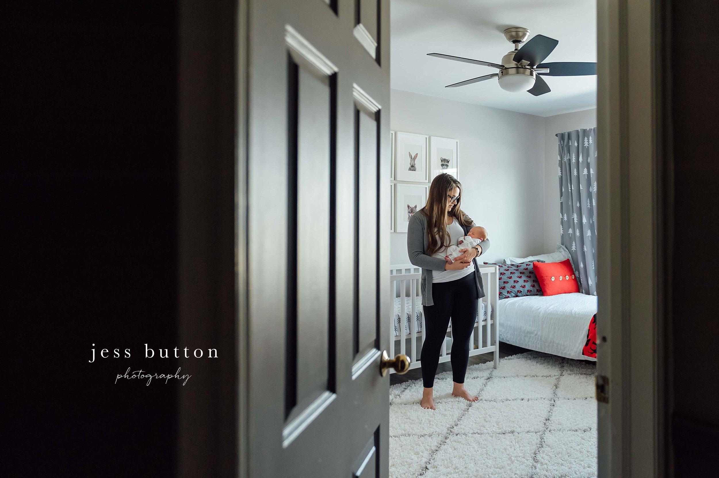 mom staring with baby in grey nursery - Niagara lifestyle newborn photography