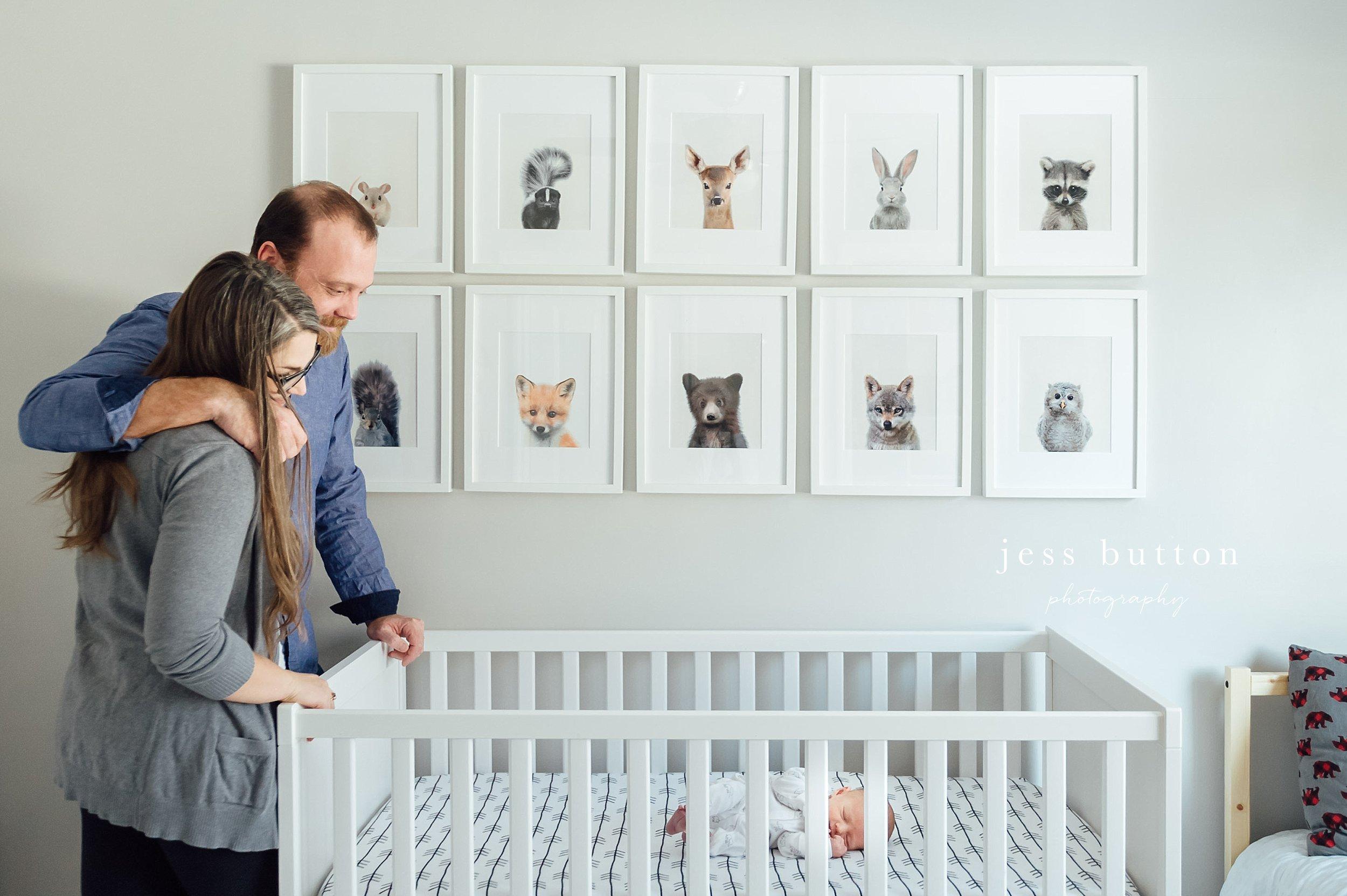 parents looking at newborn in crib - Niagara baby photographer