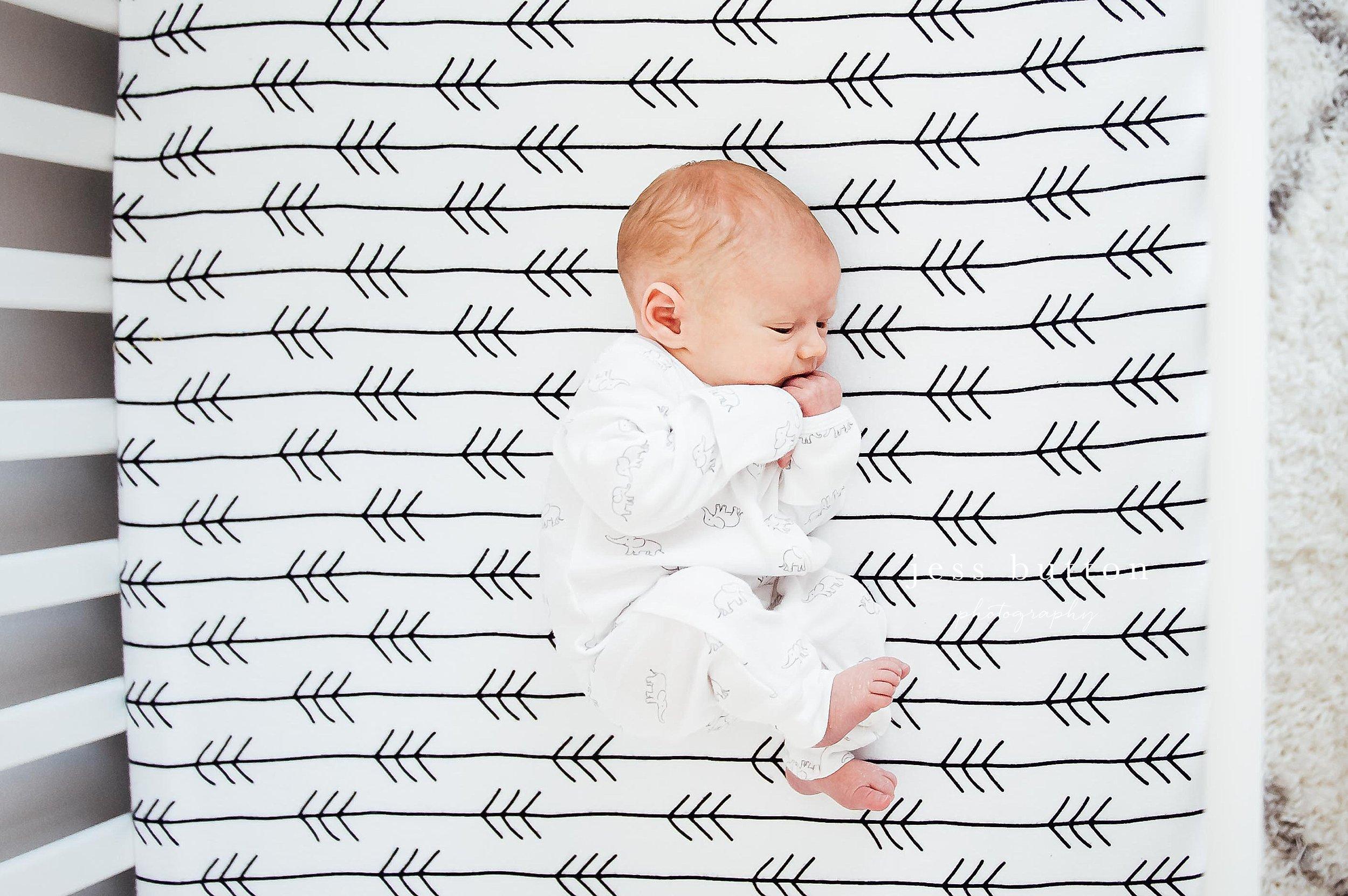 awake baby boy in crib - Niagara newborn photographer