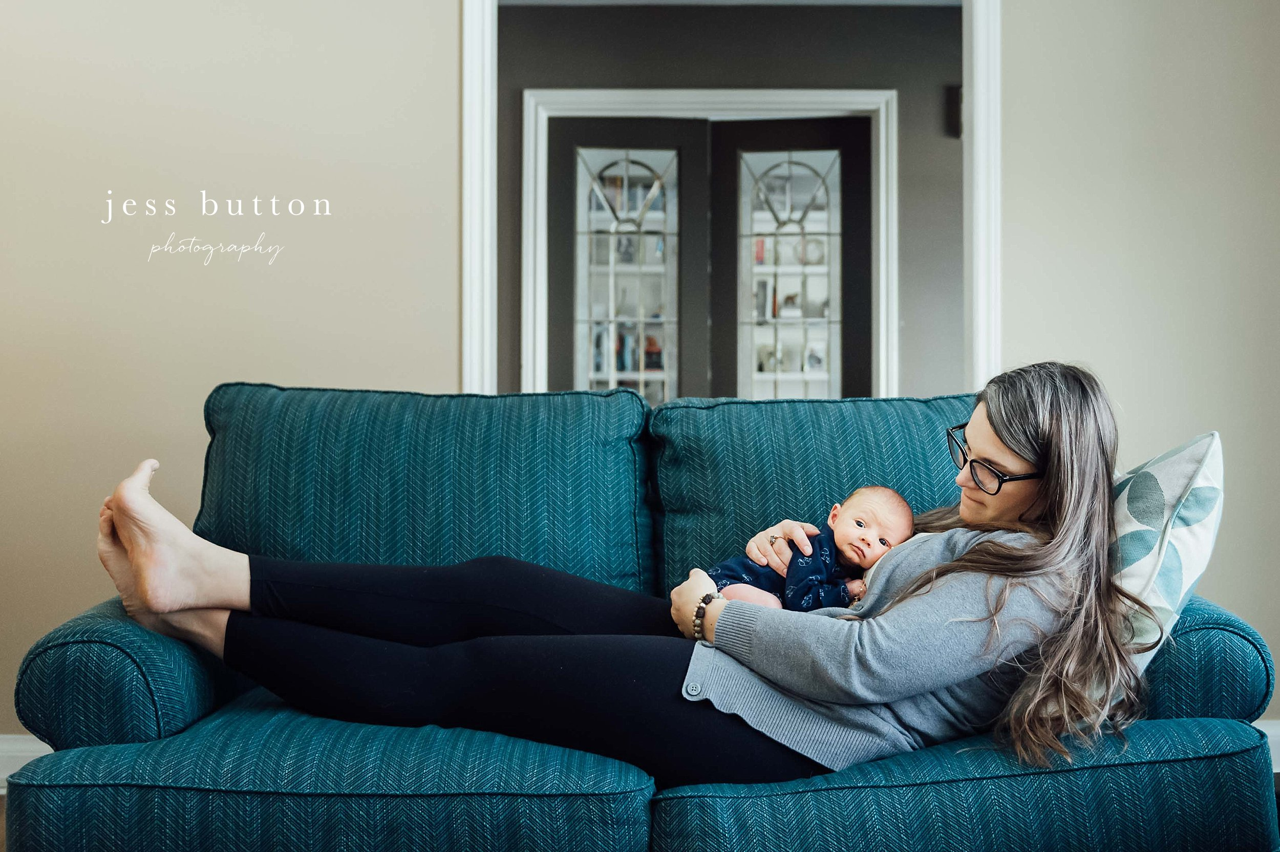 mother laying n green couch with with new baby boy sleeping - lifestyle newborn photography niagara