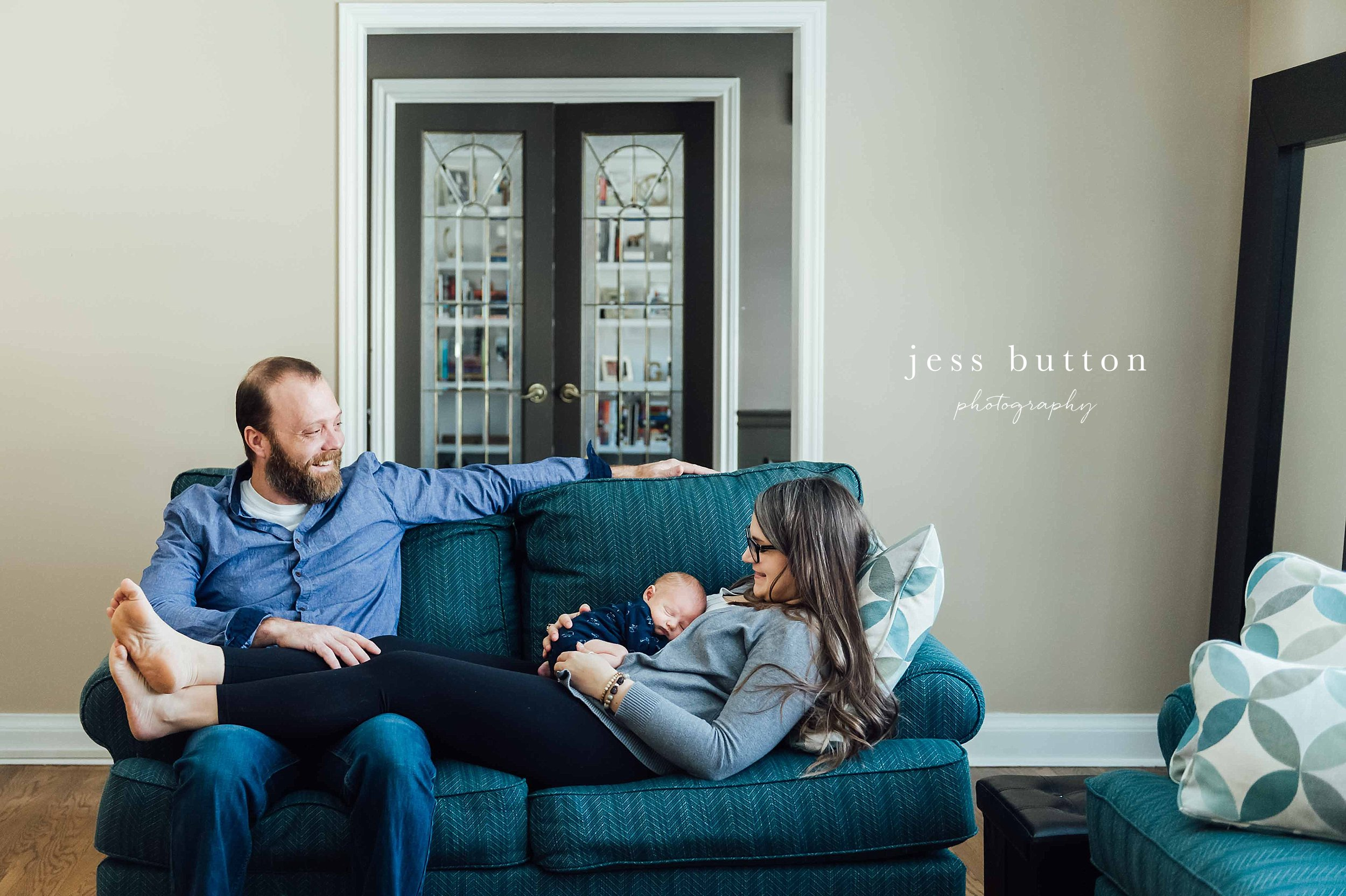 family of three on couch in home - niagara in-home newborn photographer