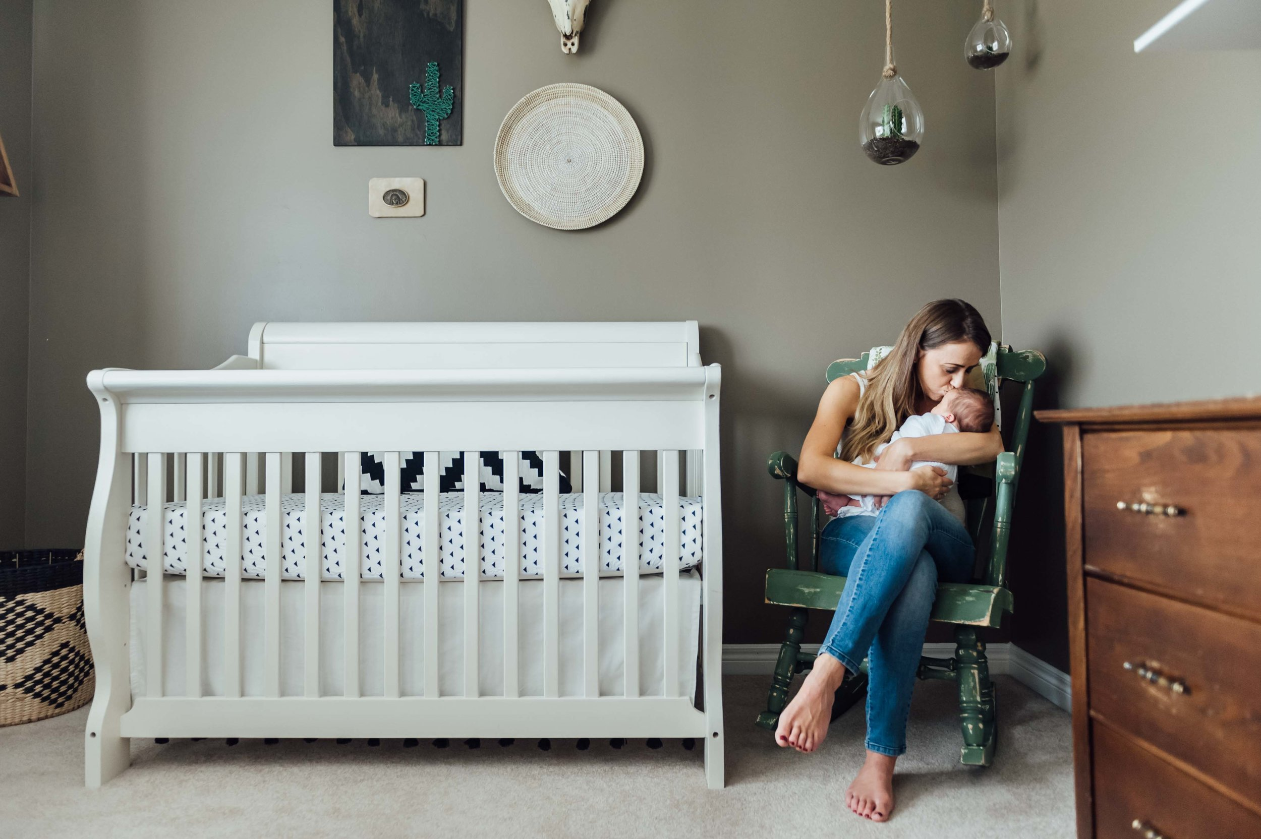 new mother holding baby boy in rocking chair - in-home lifestyle newborn photography- St Catharines, Niagara