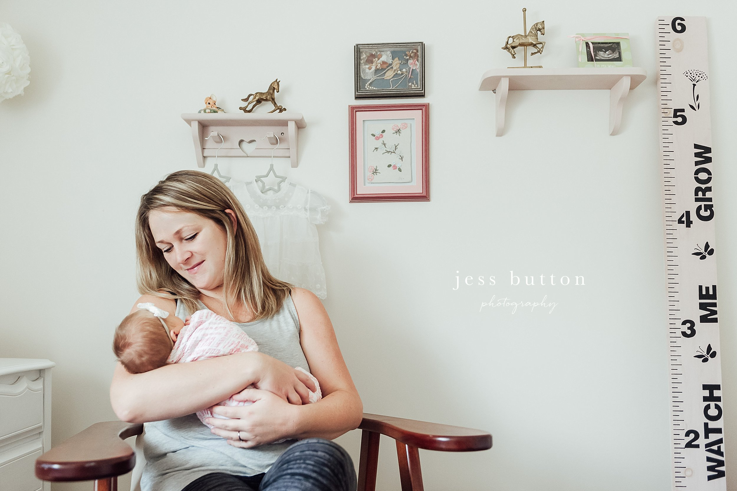 niagara newborn photographer - St Catharines baby photographer - new mother holding baby in nursery at home