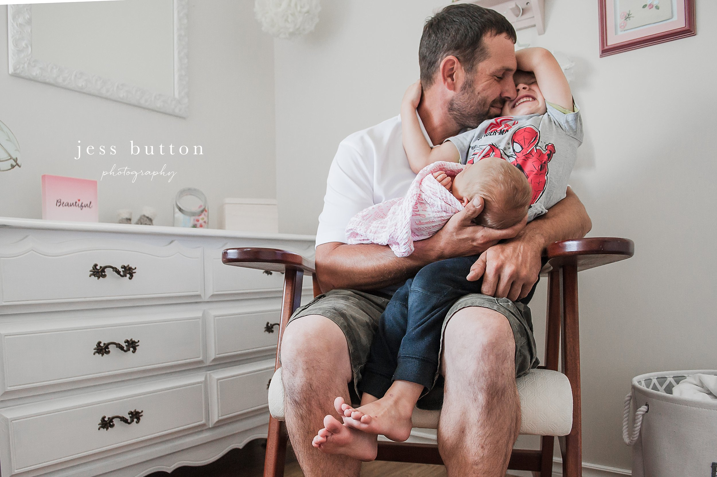 niagara newborn lifestyle photographer - St Catharines baby photos - 8 day old girl with big brother and dad in family rocking chair in nursery at home
