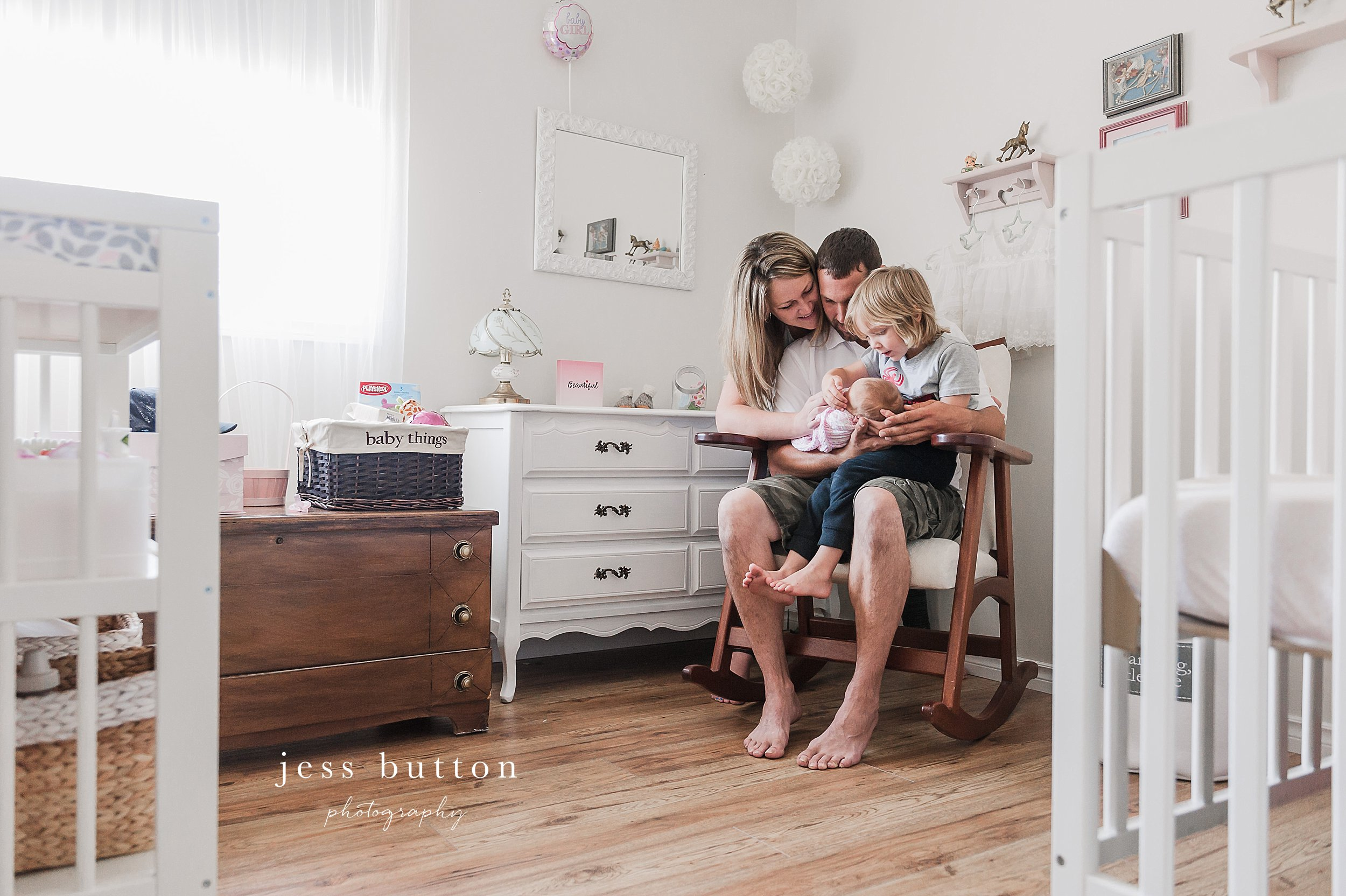 niagara newborn lifestyle photographer - St Catharines baby photos - 8 day old girl with family of four at home in pink and white nursery