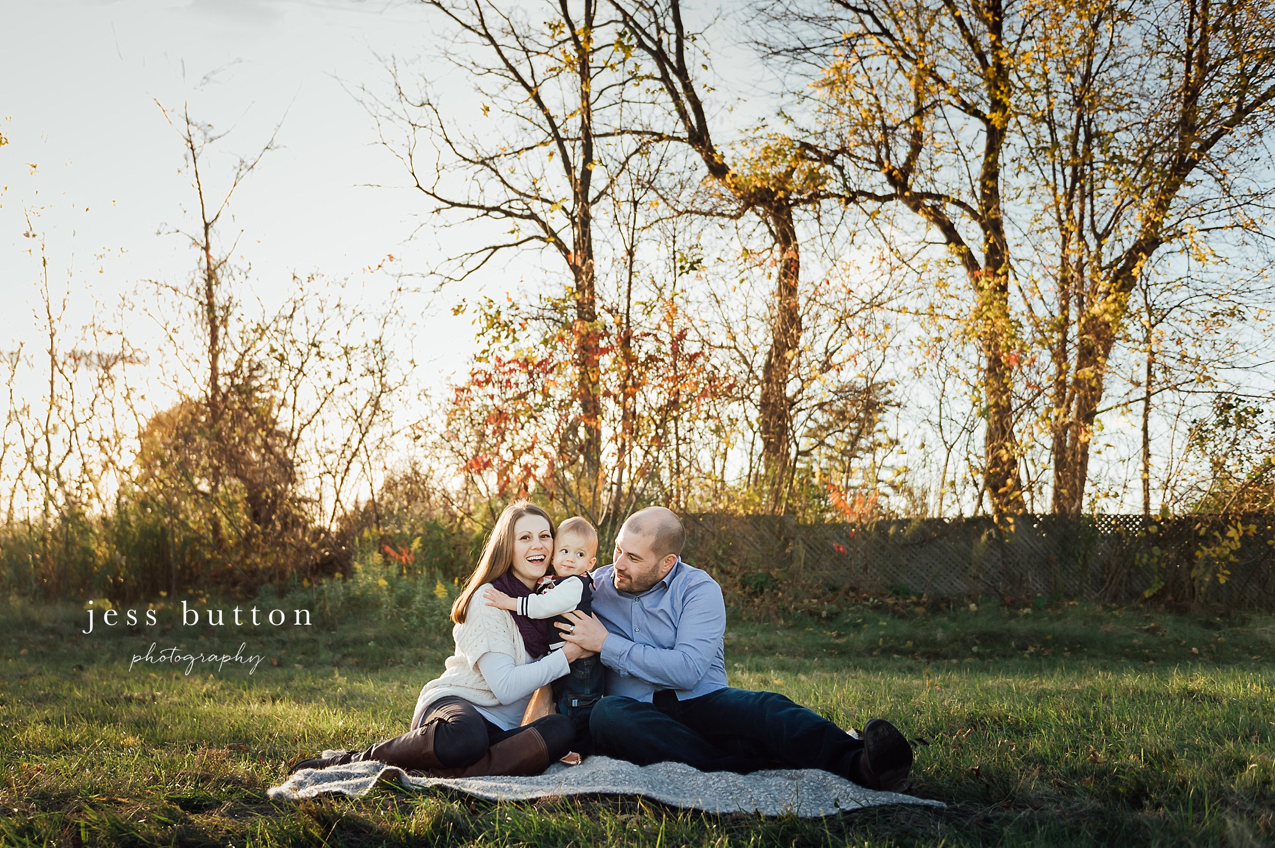 Niagara Family Photographer - photos at home in St Catharines - parents with 10 month old baby boy in field