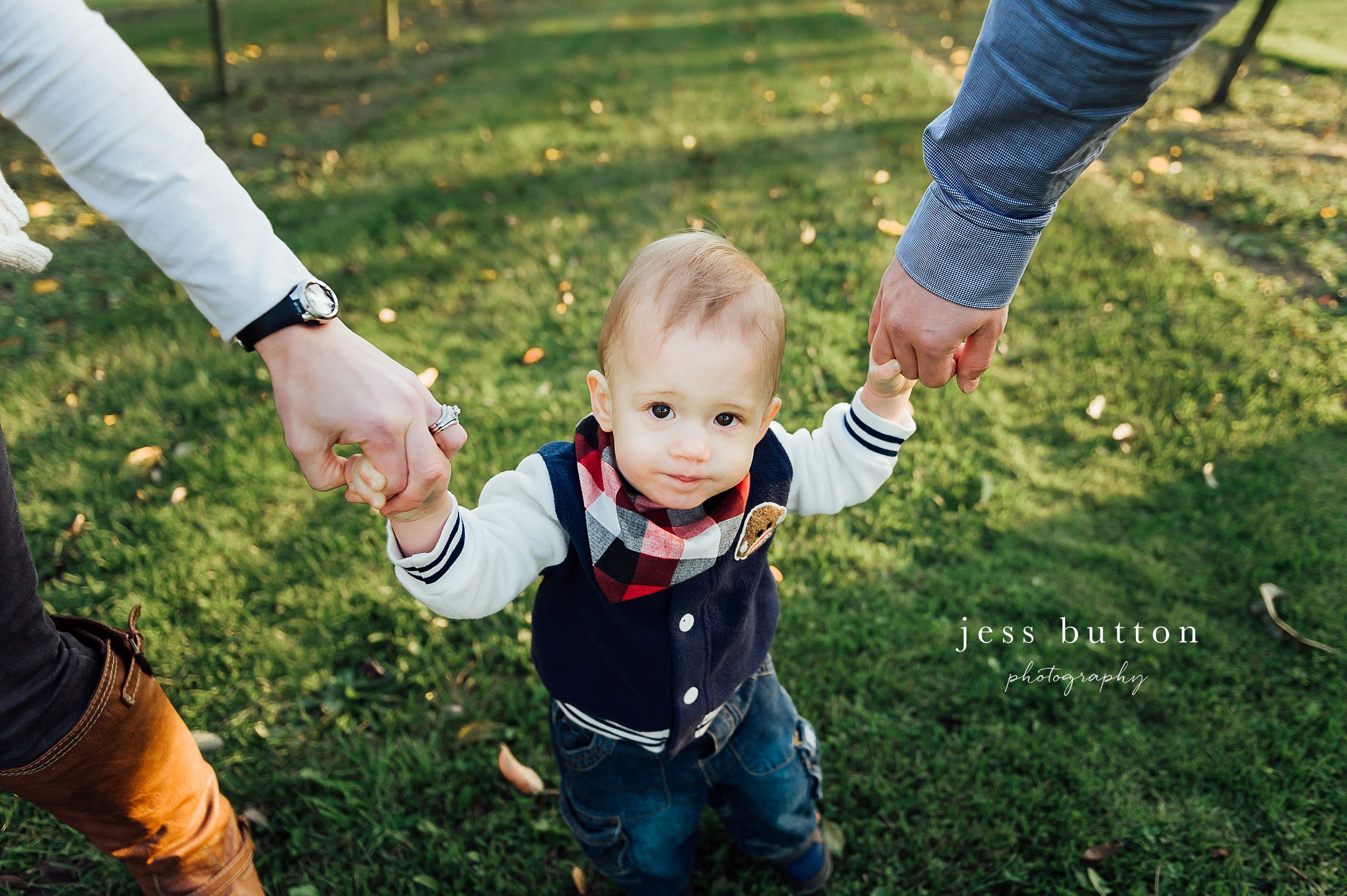 Niagara Family Photographer - photos at home in St Catharines - mom and dad walking with 10 month old baby boy in orchard