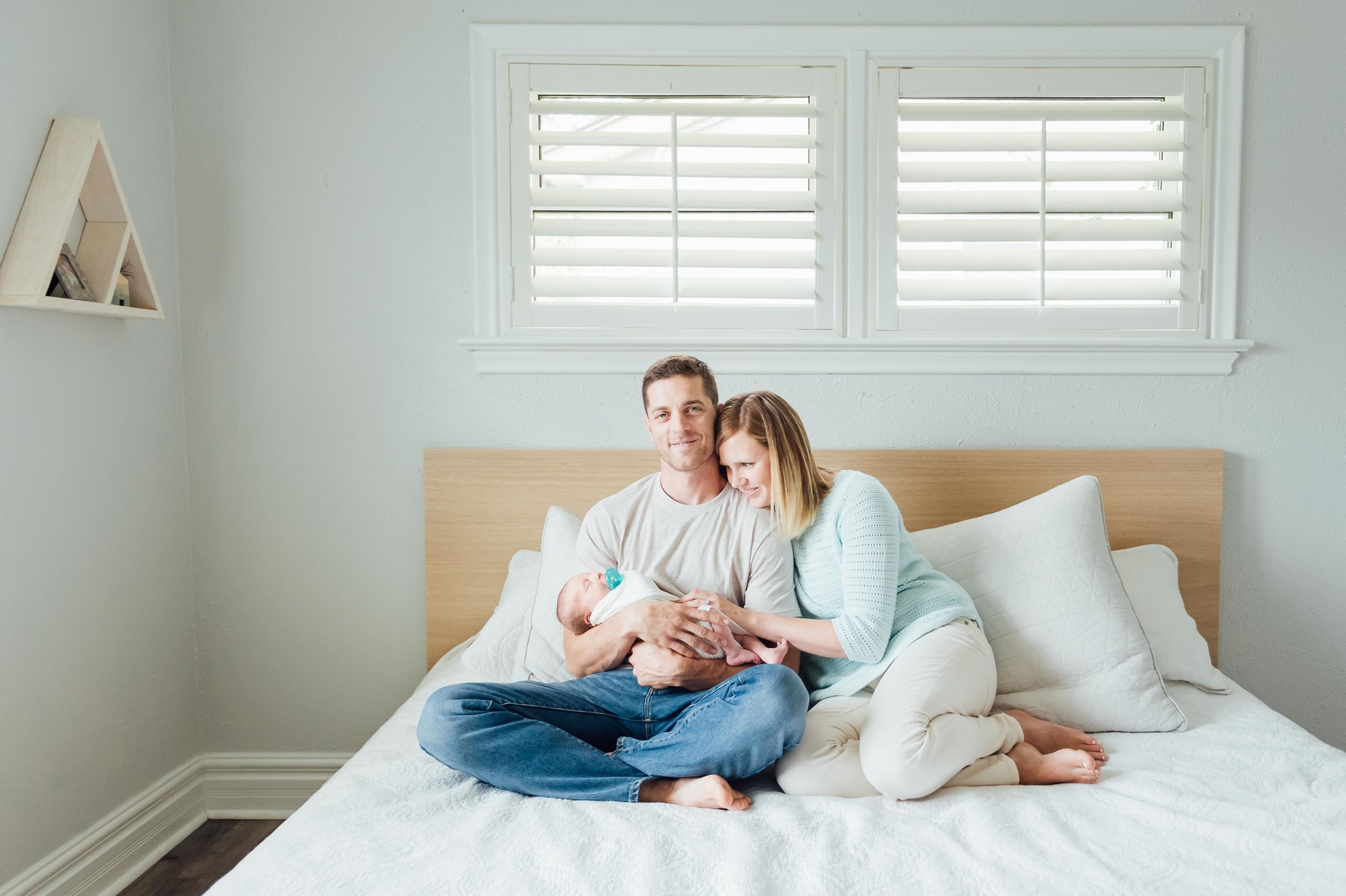 new parents with newborn baby boy at home in master bedroom - Niagara Newborn Lifestyle Photographer