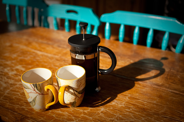 Coffee plunger and mugs on a wooden table