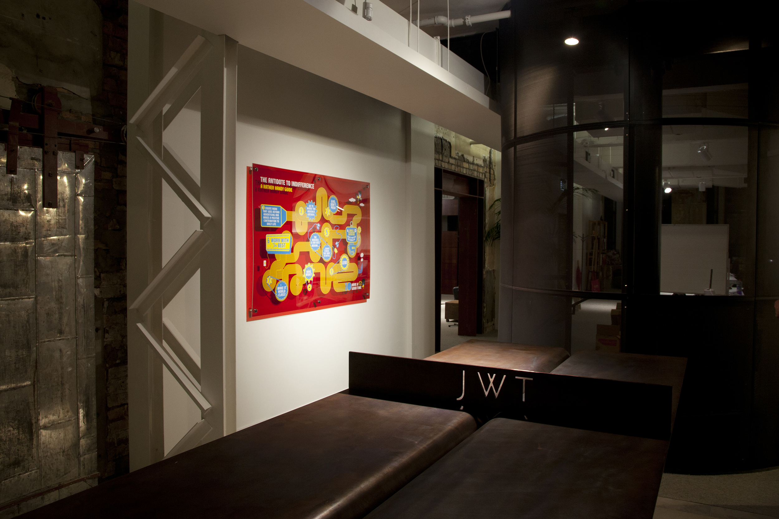 JWT interior design with a JWT sign in the foreground and vibrant artwork in the background