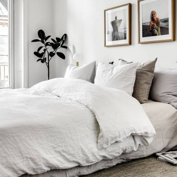 Bed with white duvet and multi-coloured pillows