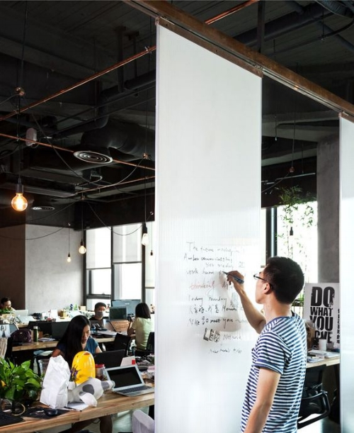 Man writing on white board while colleagues work around him
