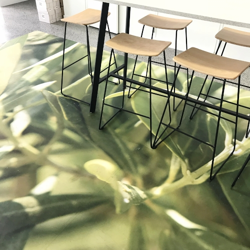 A natural plant designed rug against a monochrome table and wooden chairs