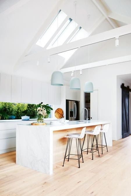 We love how calm this kitchen feels, high ceilings with incredible skylights and a touch of soft blue.. so pretty. The use of a window rather than splash back extends the room and brings the outside in.