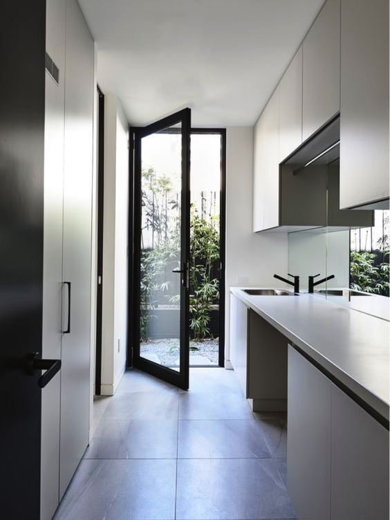 I love the use of black handles and tap ware in this laundry. They compliment the colour of the joinery, making everything look cohesive. The mirror splash back is such a smart choice in here! it reflects light really well and makes this narrow space feel a lot wider.