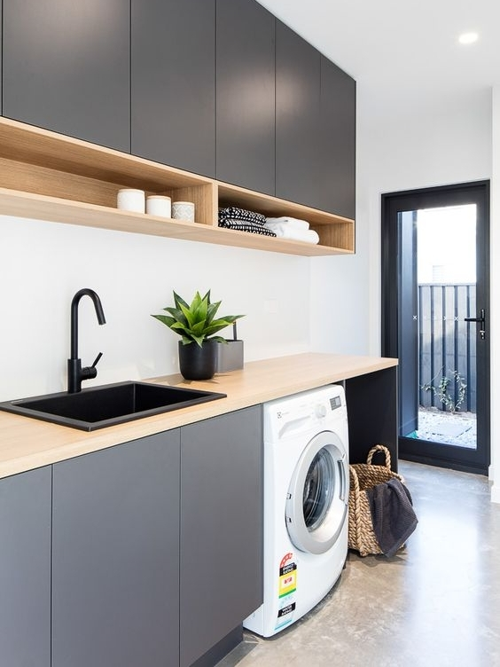 Don't be afraid to go for a laundry that isn't white! if you have the luxury of a larger laundry that has plenty of light, splash out and do something bold! I love this charcoal cabinetry, black basin and tap, they tie in with the black joinery and create a lovely flow to the outdoor area. Once again they are utilising the high ceiling for full height cabinets which is great!