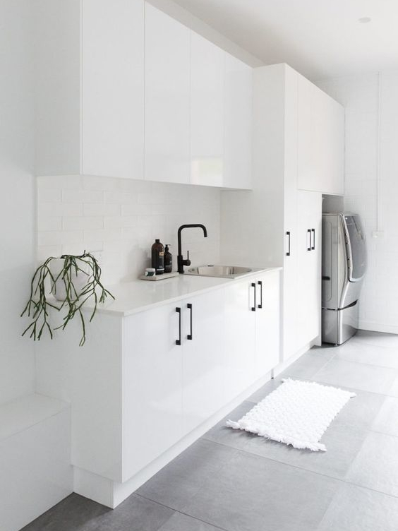This slick white laundry looks beautiful. Something like this could easily be achieved for people on a tighter budget with pre-made white cabinetry. Black handles and taps are easily assessable and affordable from home project stores. I love that they have included a full height cupboard, perfect for brooms, ladders and ironing boards.