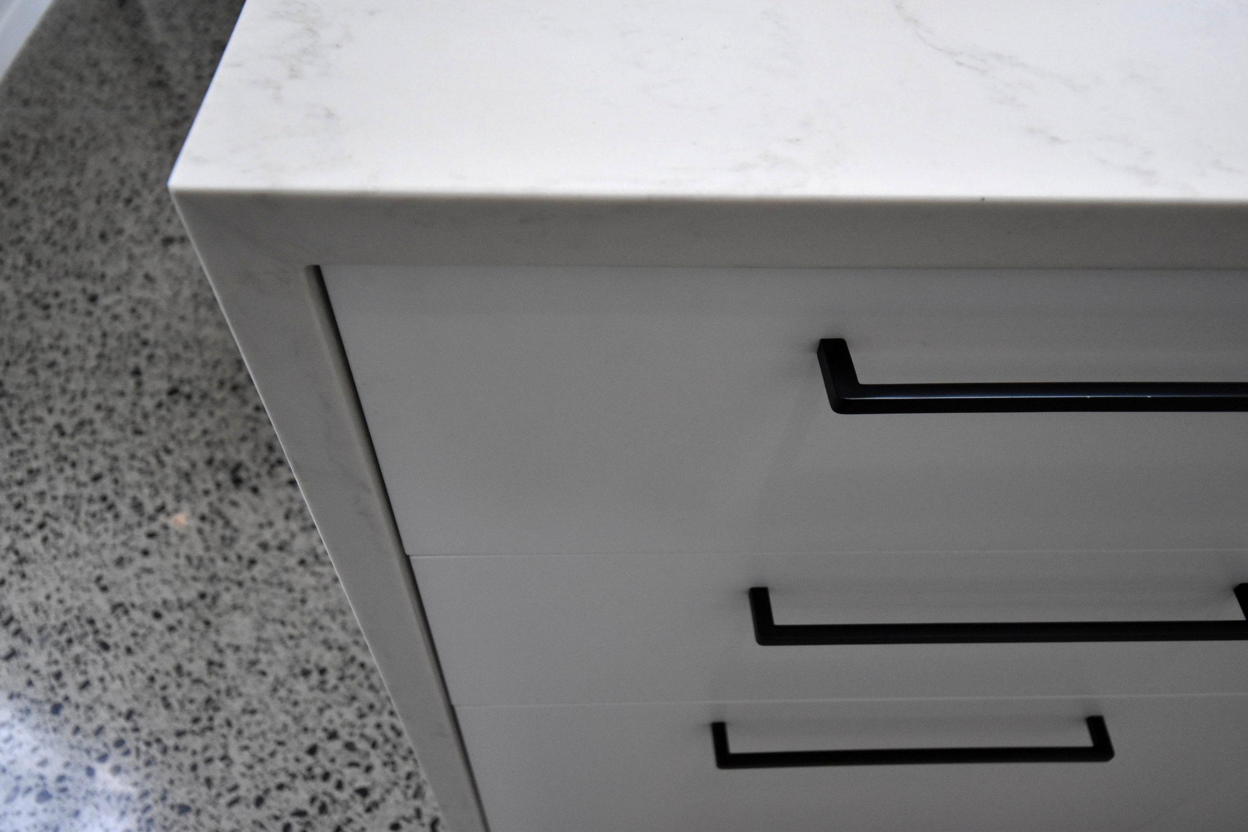 Matte white kitchen cabinetry with matte black D handles.