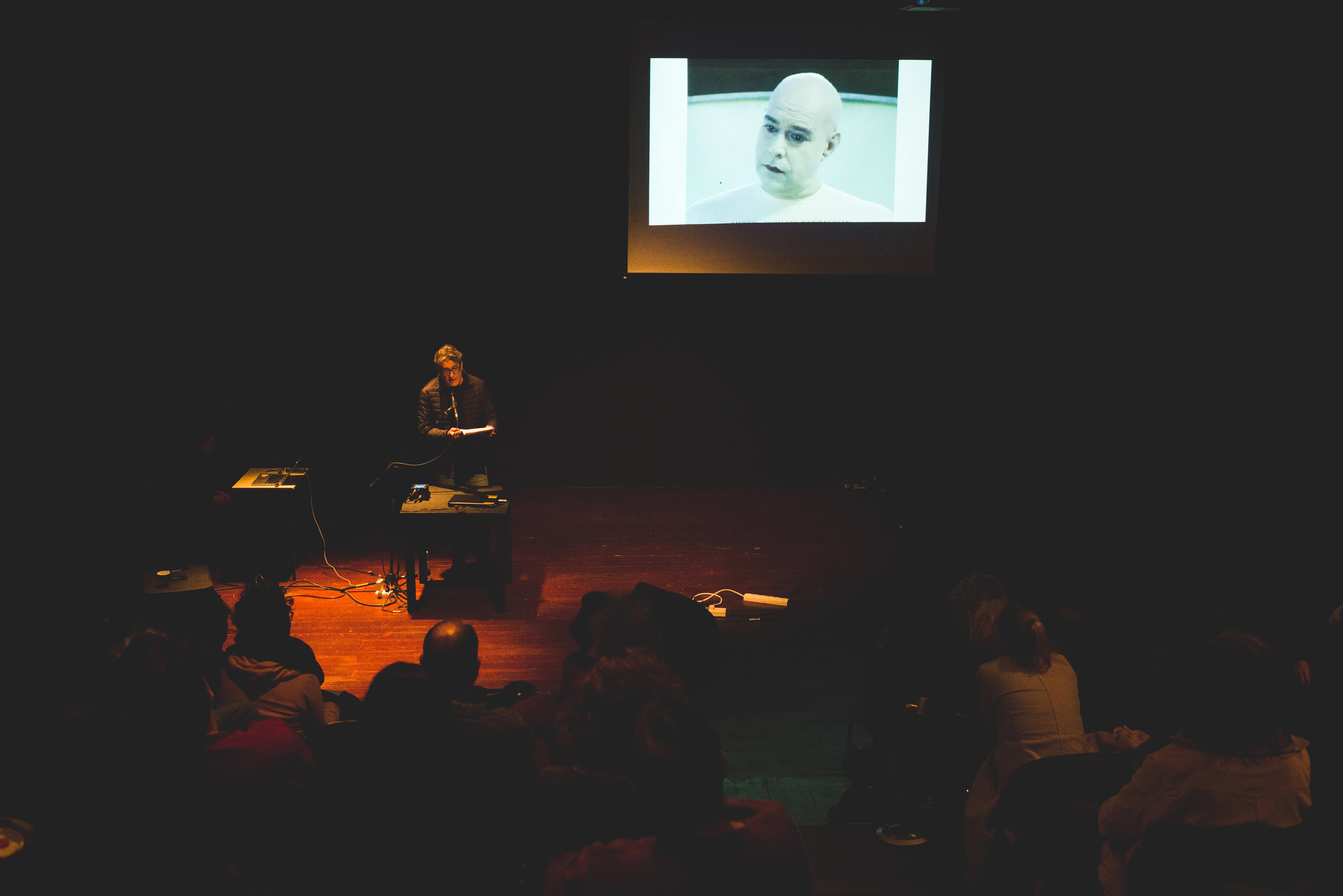 """Sergio Edelstein   In the background is a screening of Uri's video art, """"Family of Brothers"""" from 1999."""