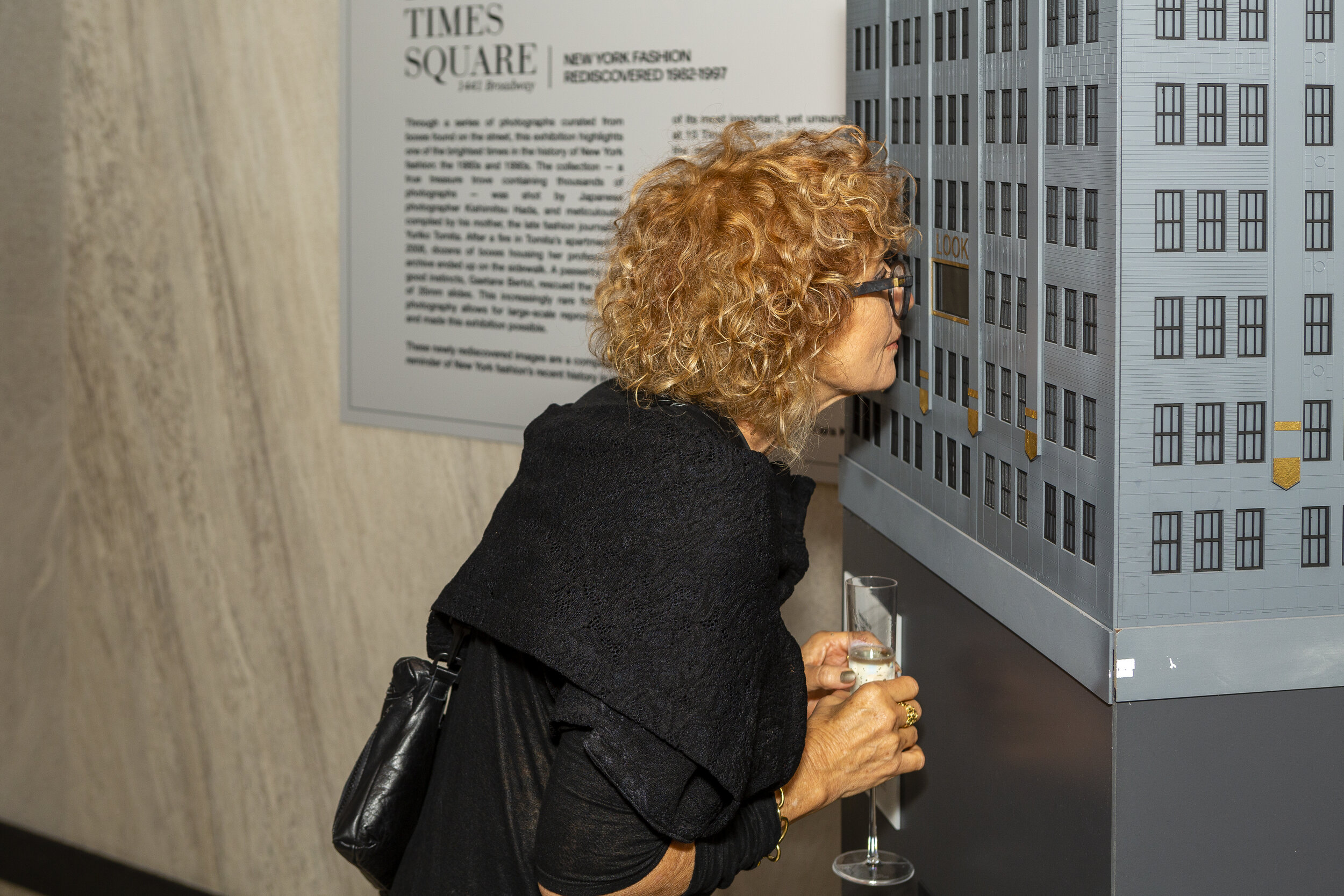 """Guest looking into the """" Shadow box """" at the opening reception."""