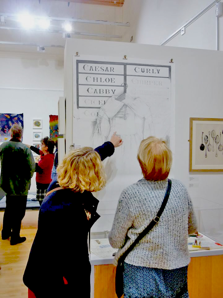 Visitors to the exhibition looking at my drawing of a farmers smock.