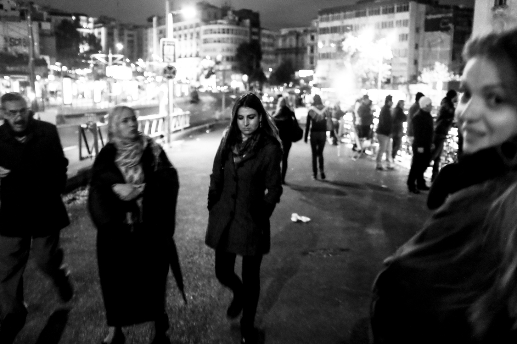 Black and White Street Photography in Istanbul Turkey. The eye is drawn here from the intended subject, the girl in focus ahead, to the out of focus face to the right this is looking at the camera.