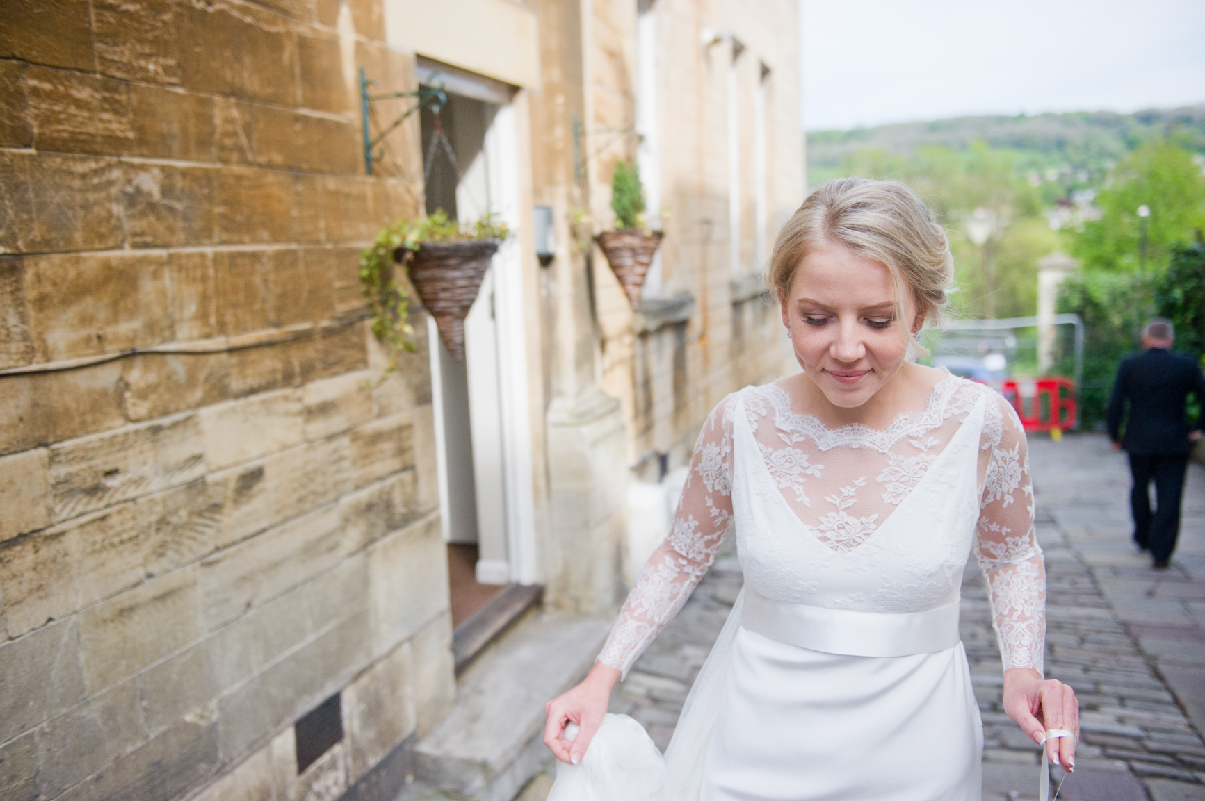 Rosie on exiting the prep venue. You can see in the background the beautiful sandstone of the buildings and the stunning backdrop of the Bath countryside beyond. Rosie is wearing Lace and a cheeky smile.