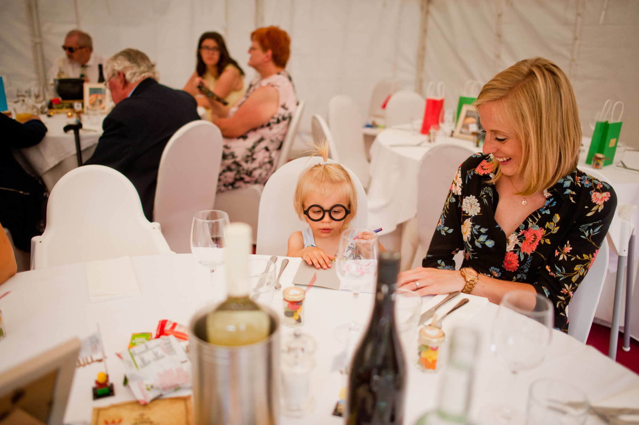 Kid at a harry potter themed wedding with potter glasses on.