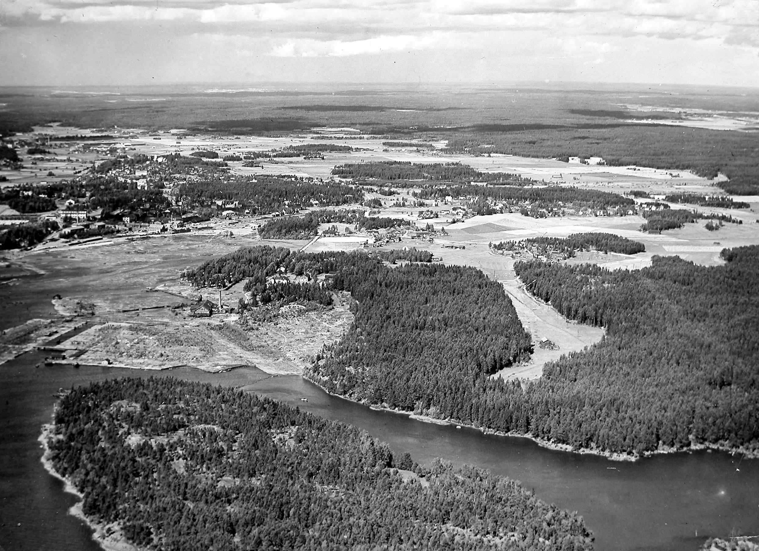Ilmakuva Sunilasta ennen sellutehtaan rakentamista. Edessä Pyötisen saari, jolle tehdas rakennettiin. © Sunila Oy:n arkisto.