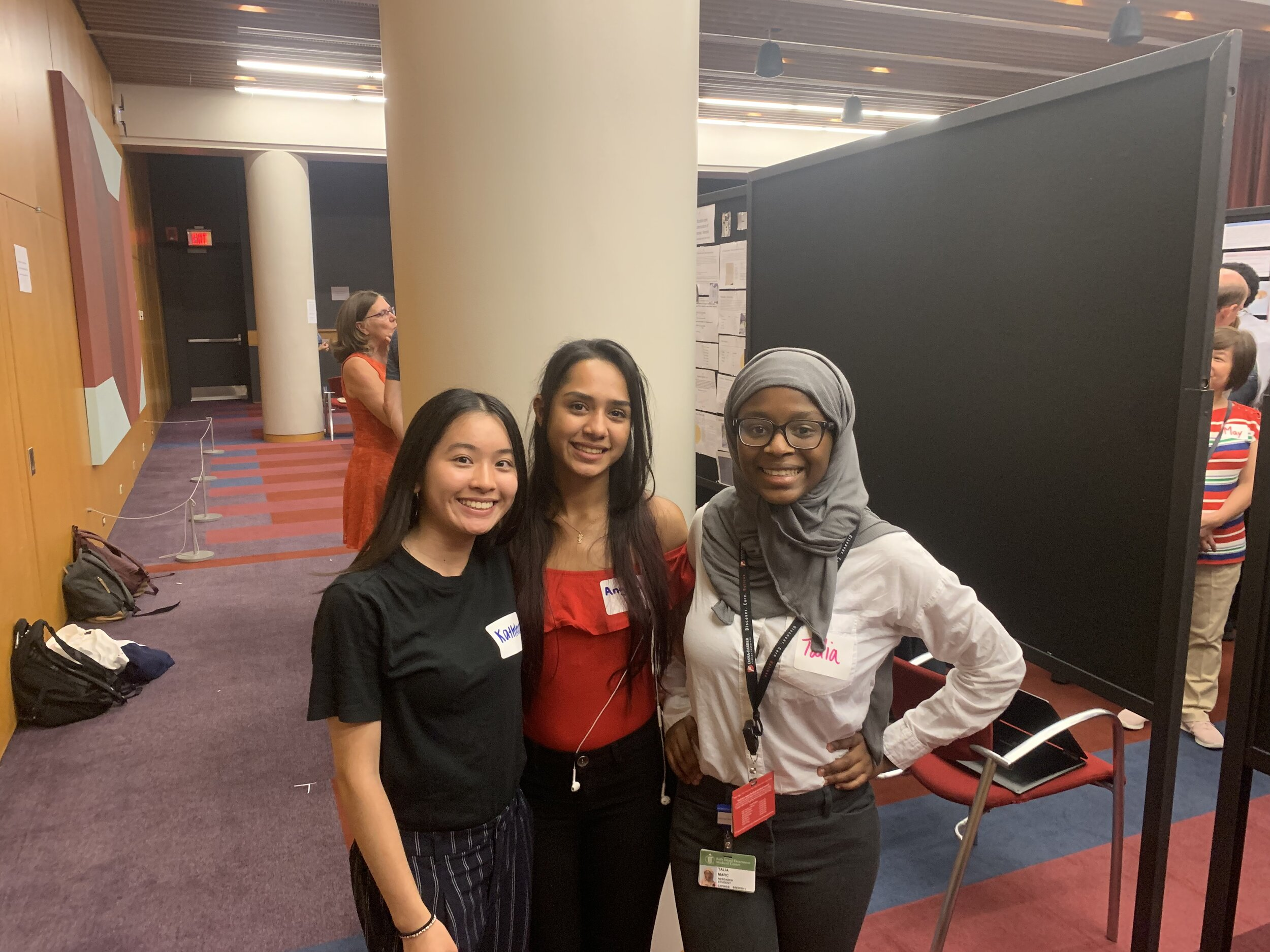 Kathleen Wei (left), Angelys Matos (center), and Talia Marc (right) sharing good times after presenting on their second year lab internships at the symposium.
