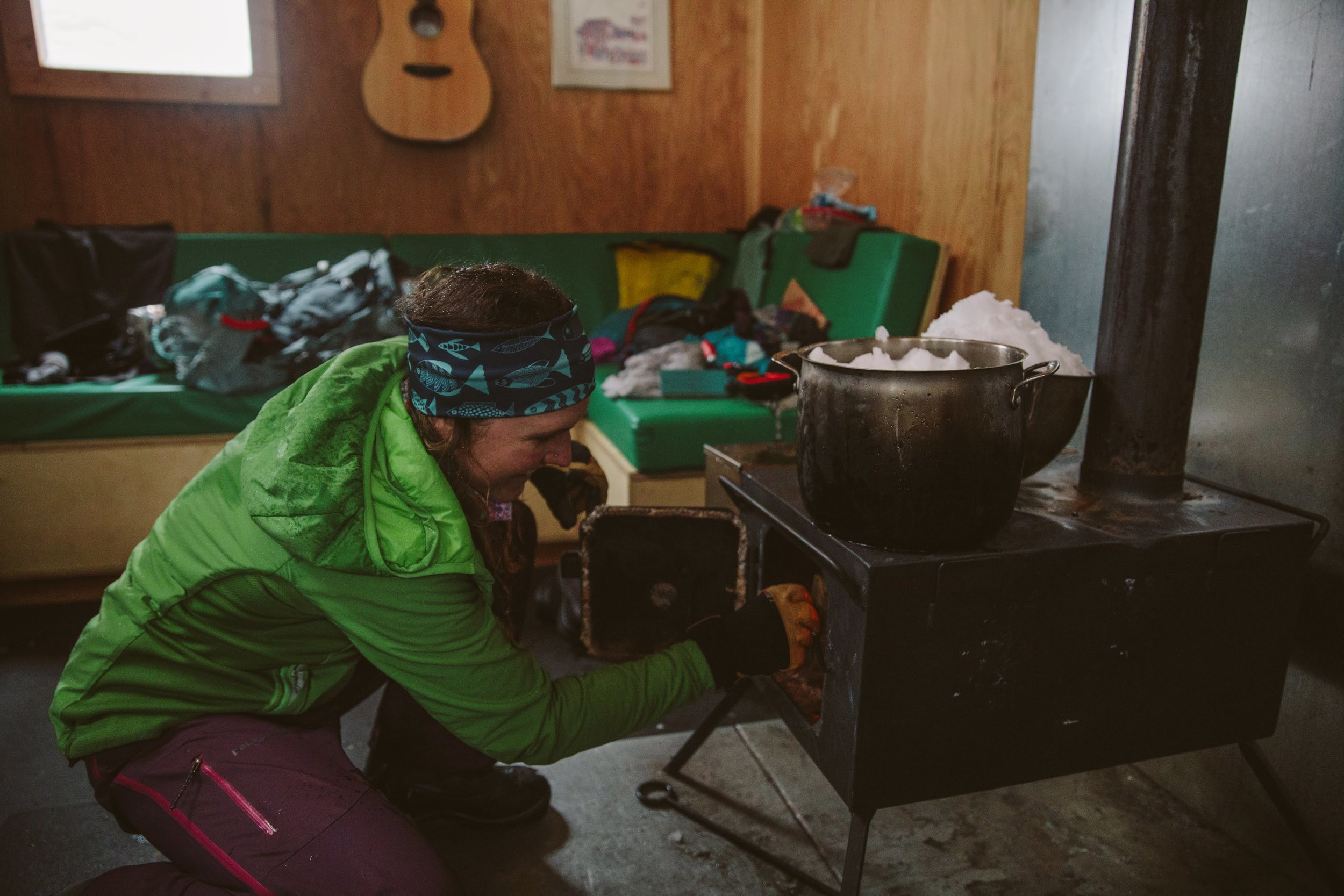 Elise adds wood to the fire so we can melt snow. Photo by Elena Pressprich (@findmeoutside)