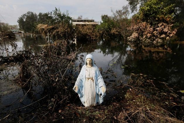 A Statue of the Virgin Mary stands in flood waters in Plaquemines Parish in Braithwaite, Louisiana. Photo credit: Mario Tama