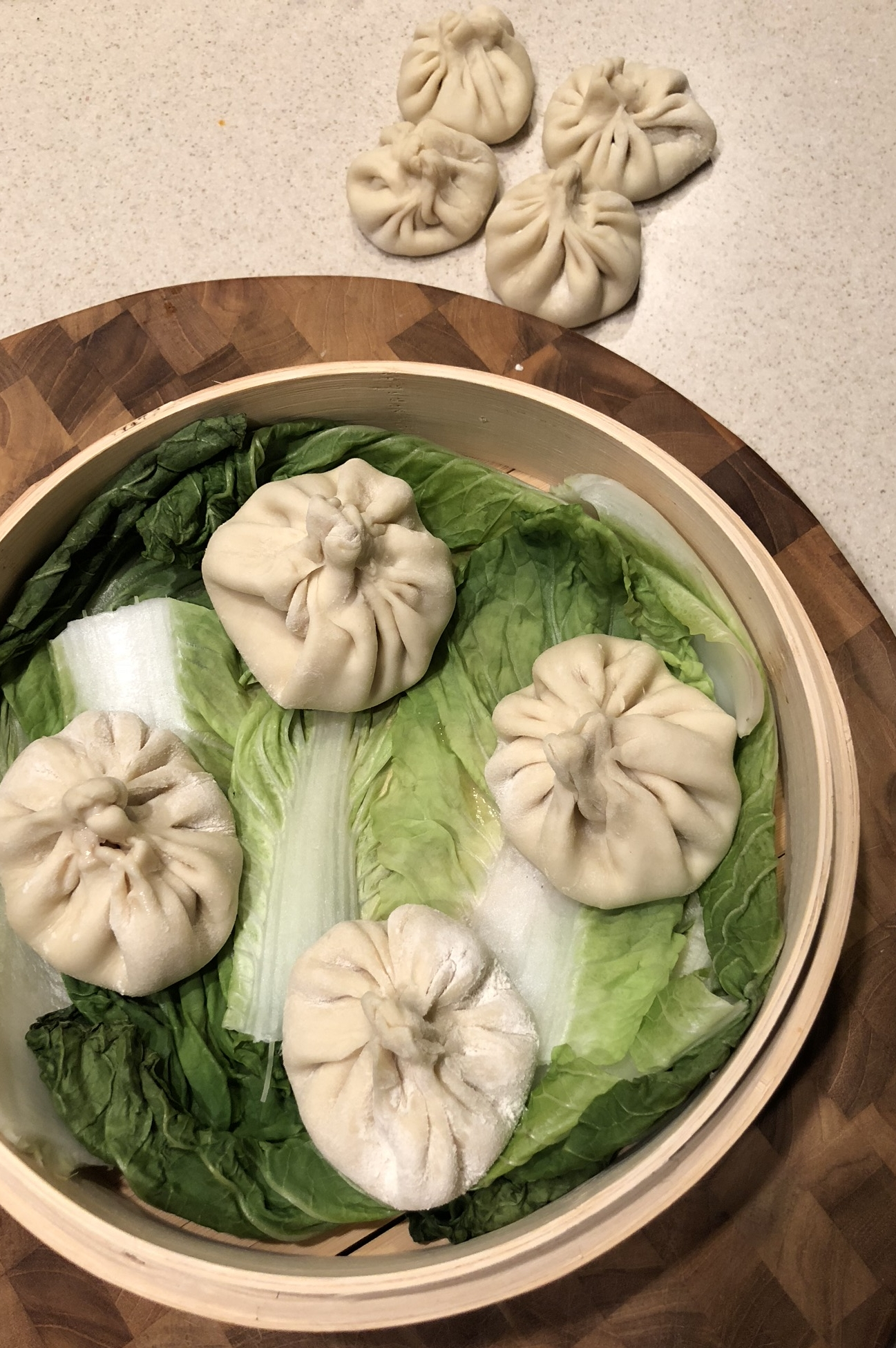Placing the freshly made dumplings onto the cabbage leaves just before steaming.