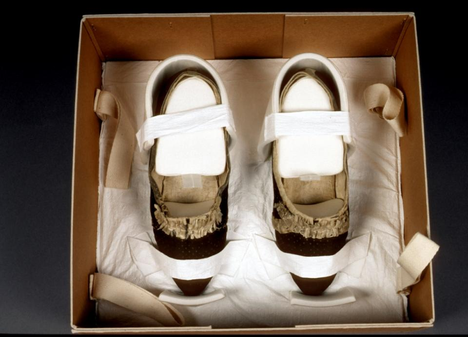 Immobilised shoes protected within an archival quality storage box