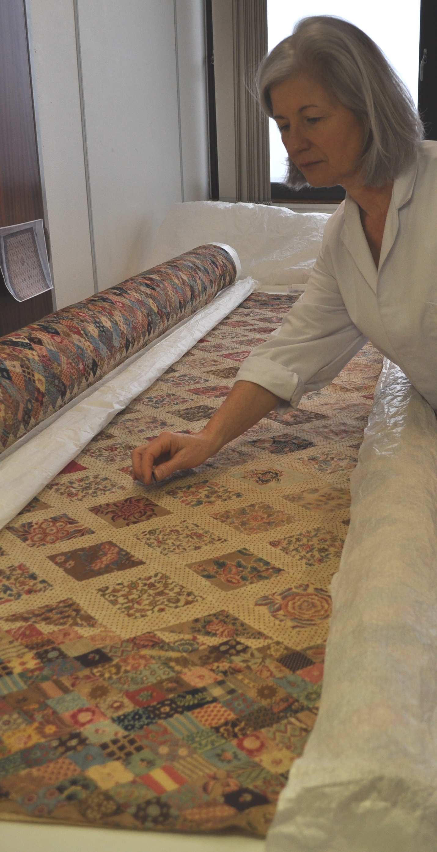 Kate Gill in the process of examining the coverlet, during conservation treatment