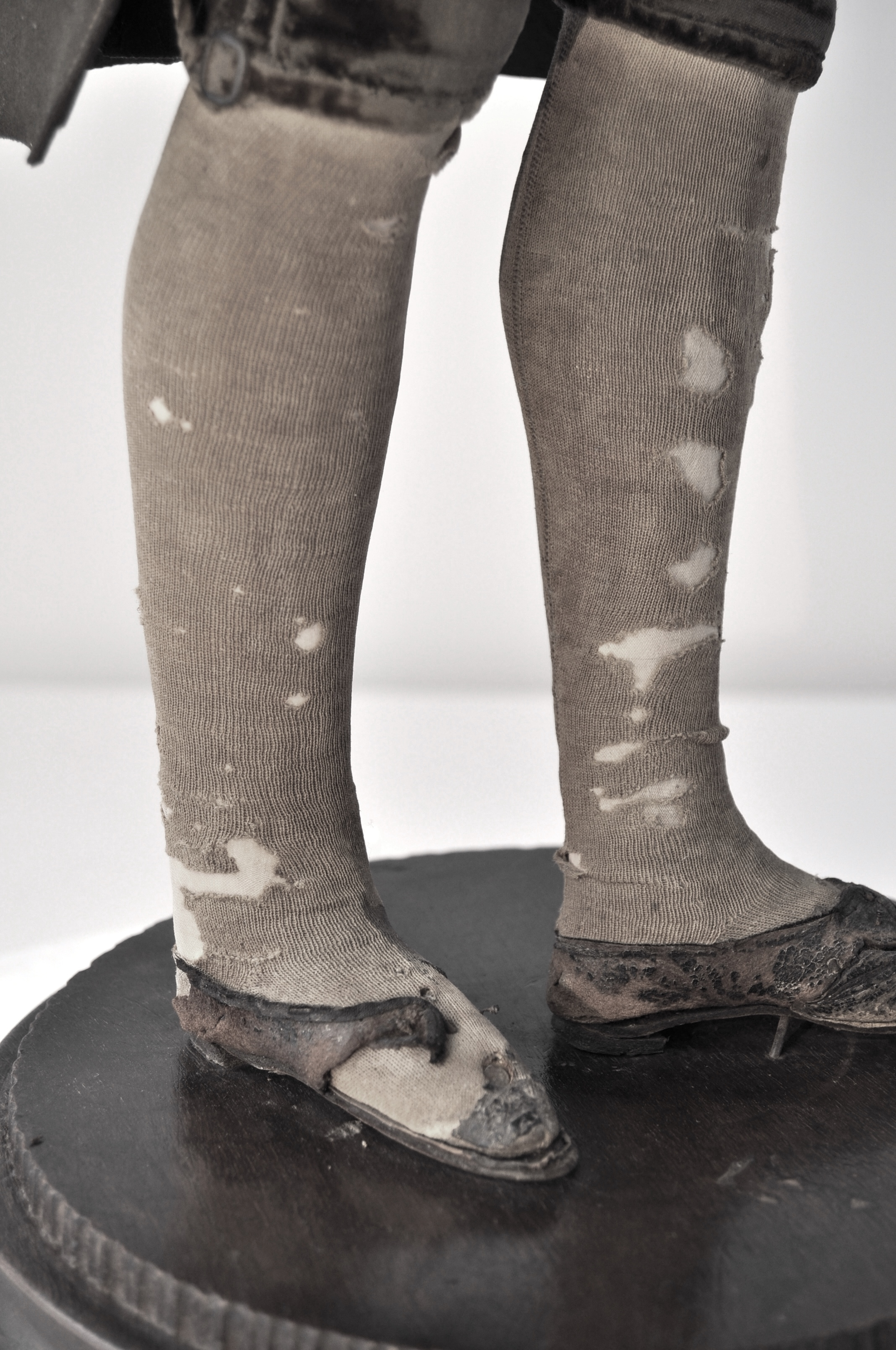 Detail of the holed silk stockings and fragmentary leather shoes, after conservation treatment