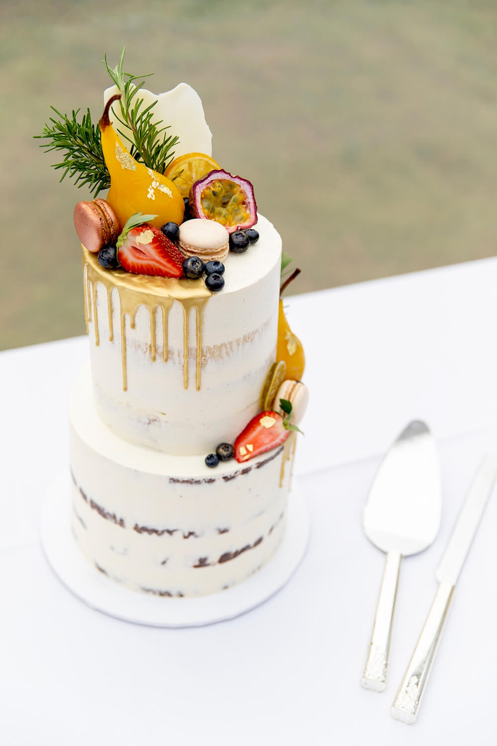 Semi naked cake decorated with seasonal fruit and handpainted gold drip