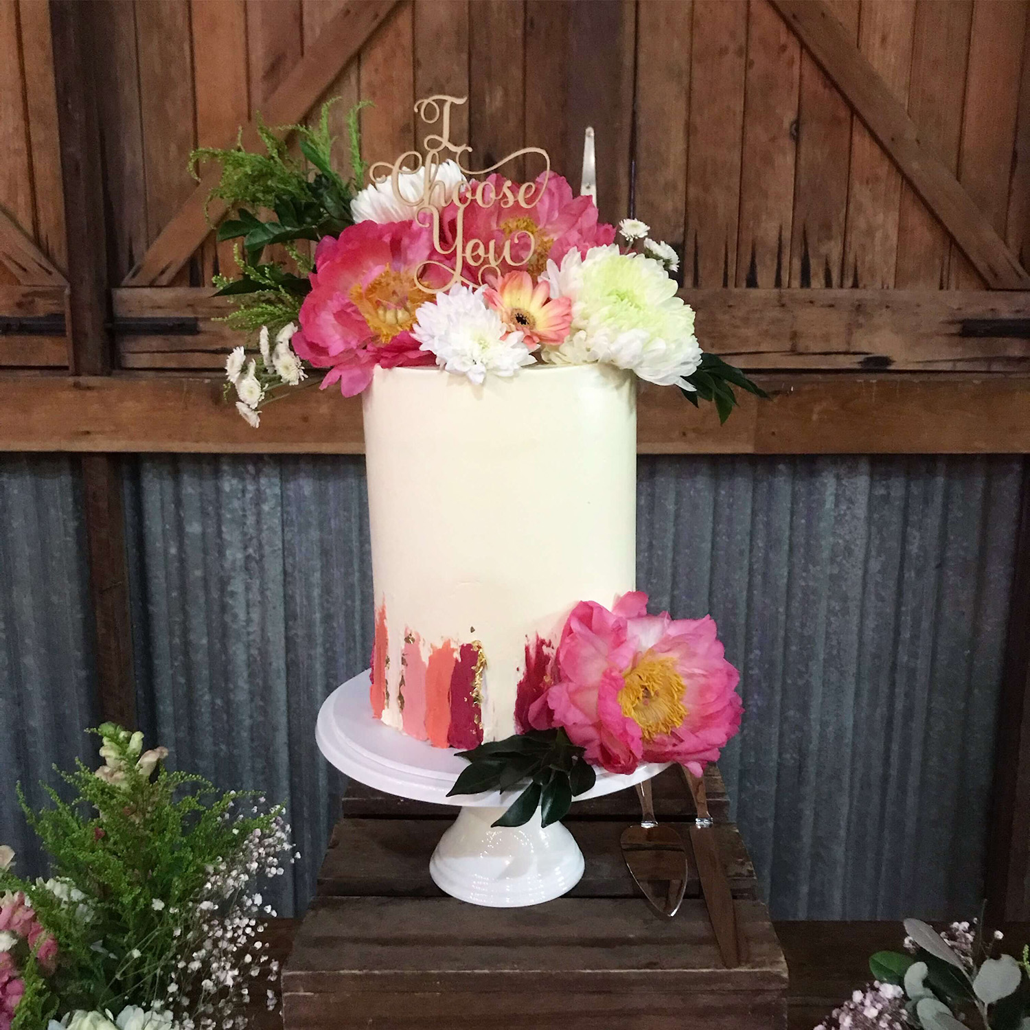 Colourful wedding cake decorated with vibrant peonies and oil paint buttercream strokes