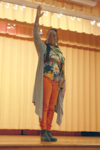 "- Poet Glenis Redmond gestures to the crowd at Rochelle Middle School during a spoken word poetry performance on April 7, 2017. Redmond stayed in the Arts & Cultural District as part of a two-week residency at Rochelle ending with an anthology of student-created poems titled ""Bad and Beautiful."""