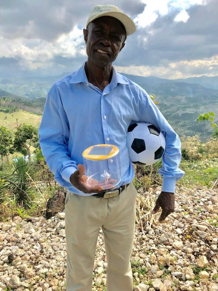 Pastor Felix accepts solar lamps to bring light to the community
