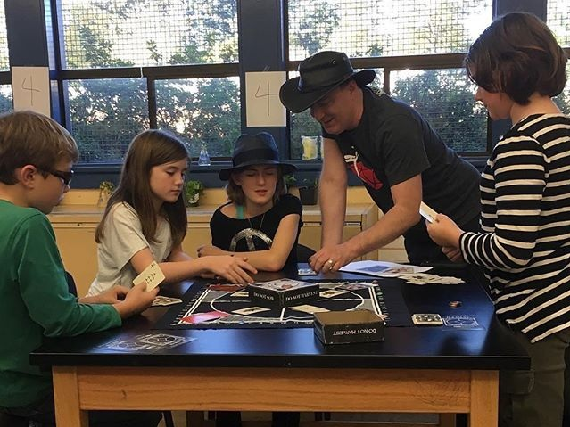 Designer Keith Baker play testing Illimat with a middle school game design club in Portland, OR