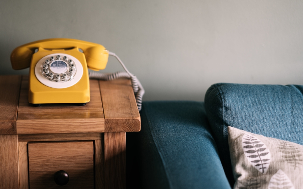 Vintage yellow phone sitting on an oak side table next to a clean denim sofa.
