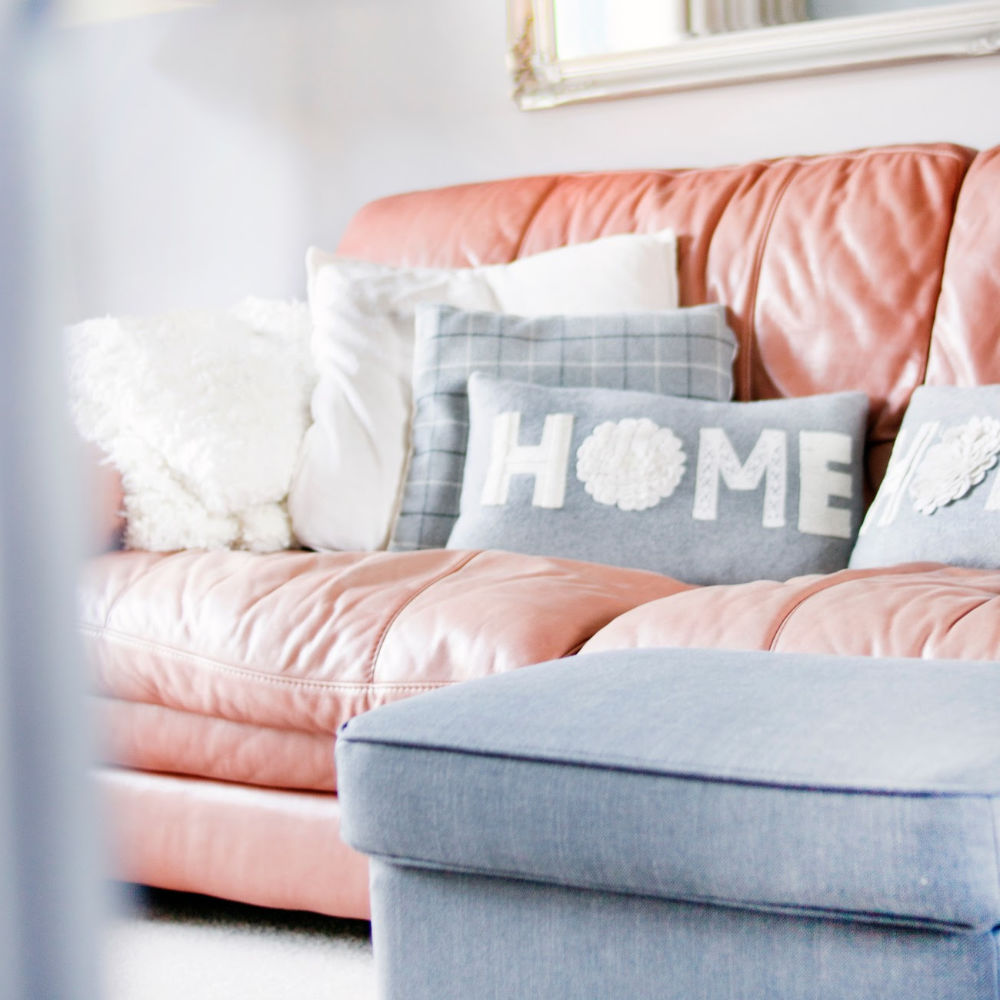 Couch and ottoman in cozy, clean living room with a pillow that reads 'home'.