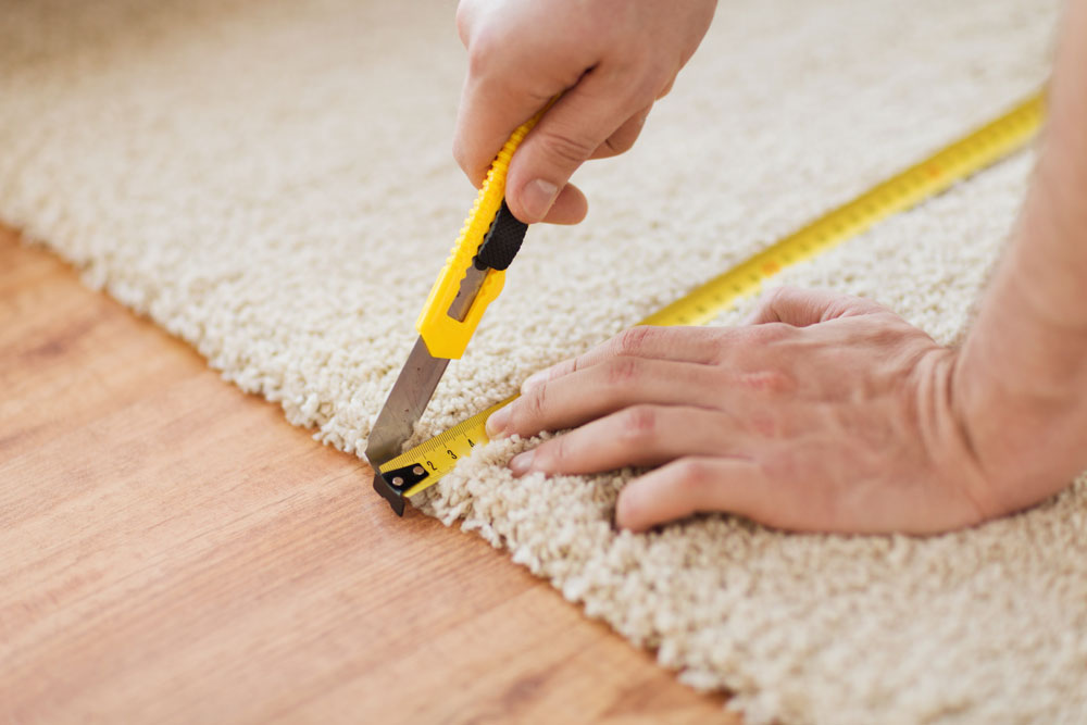 Close up view of technician measuring and repairing carpet