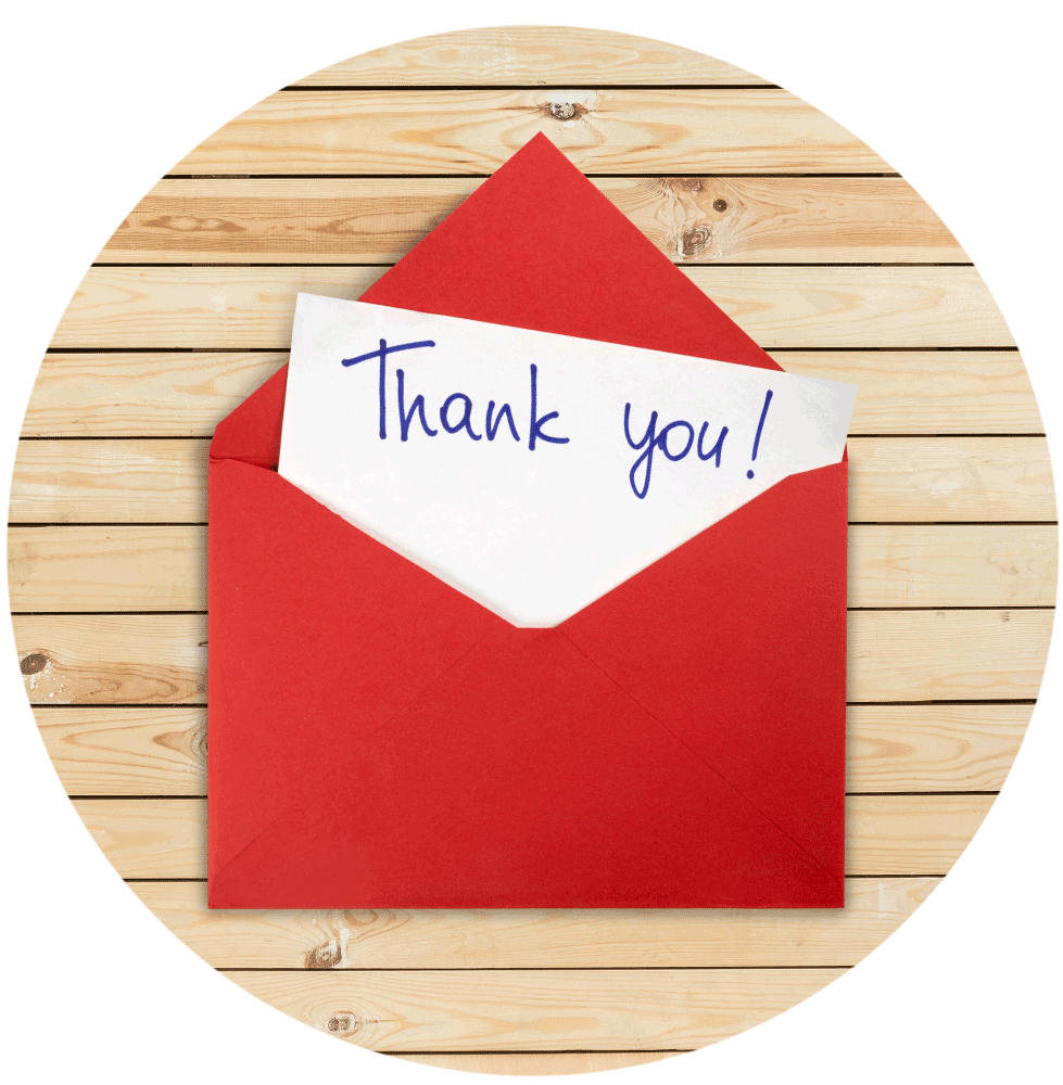 Thank you note in red envelope on wooden slats.