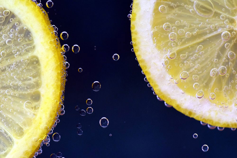 Lemon slices in clean water with air bubbles.