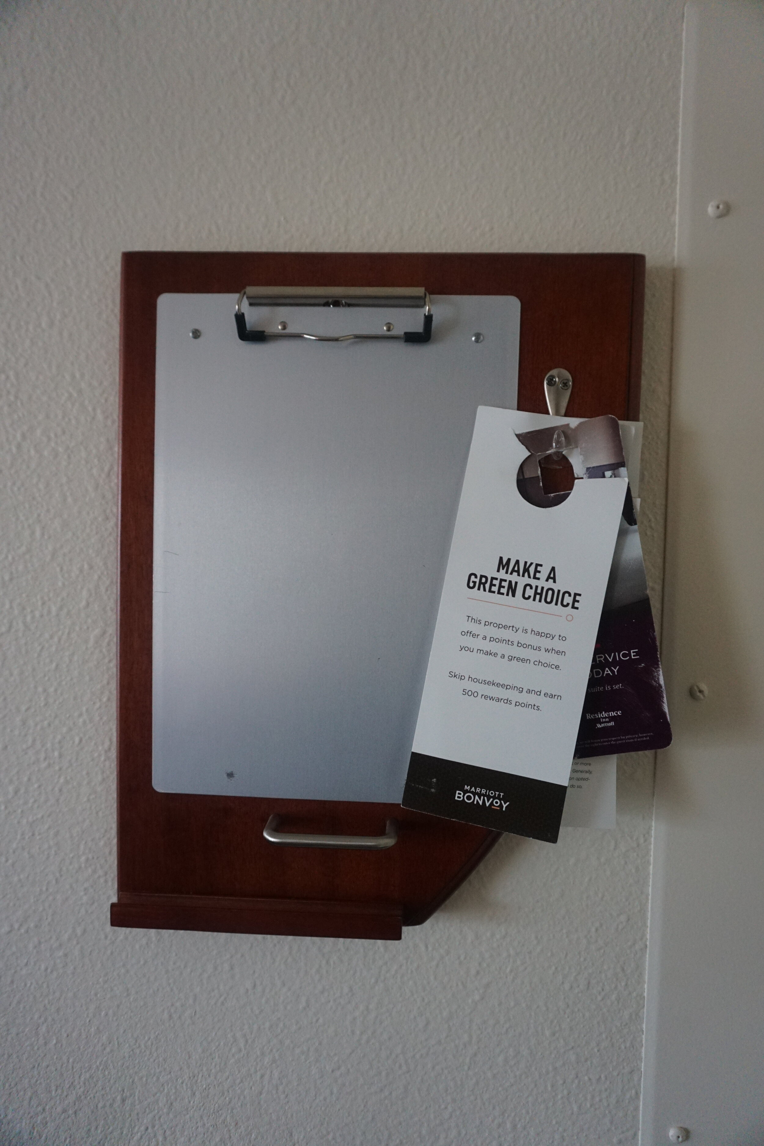 """Clipboard by the door, this hotel still offers """"make a green choice"""" for skipping housekeeping"""