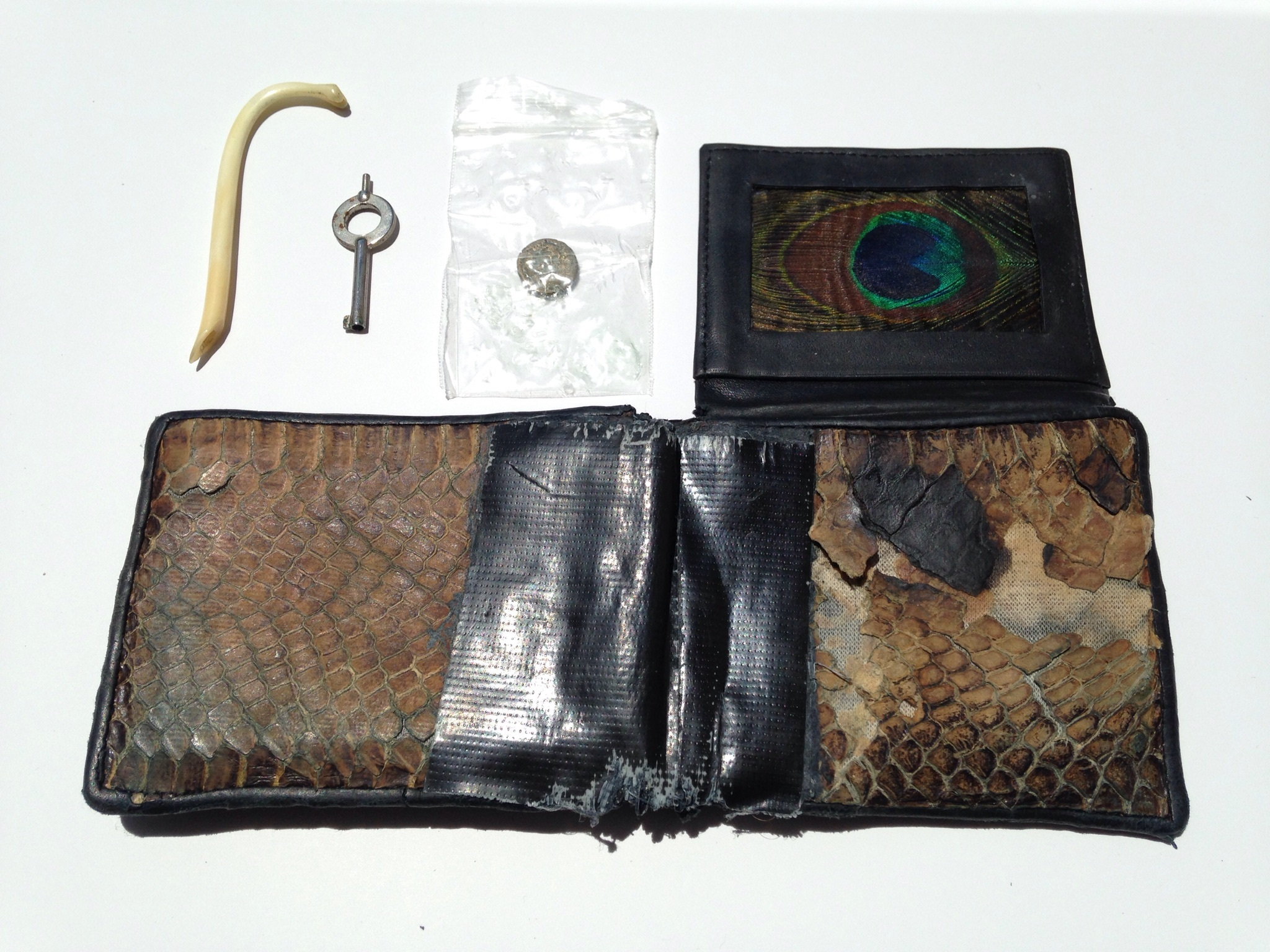 Untitled (Wallet I),  2013 Cobra skin wallet, duct tape, peacock feather, coon-dick toothpick, Smith & Wesson police issue handcuff key, 4th century BCE Greek coin depicting Dionysus 7.5 x 8.5 inches