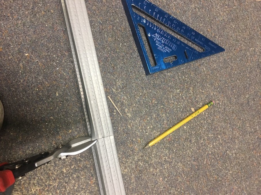 Cutting steel studs with tinsnips.